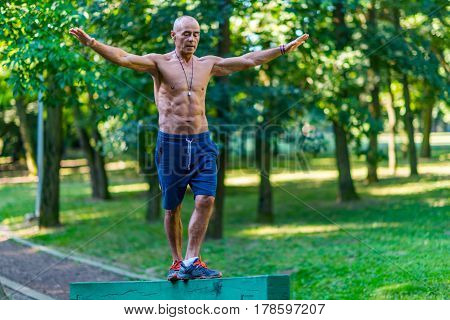 Senior Male Exercising Outdoors In Public Park