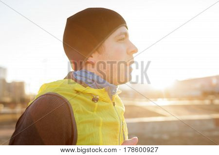 A Young Man In A Hat And Bright Jacket Runs In The Morning At Sunrise. Play Sports And Lead An Activ