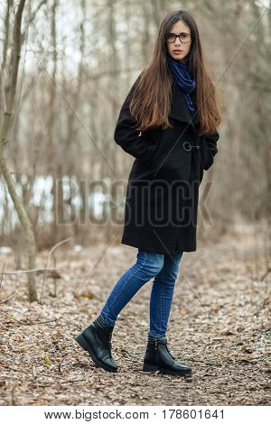 Young Beautiful Girl In A Black Coat Blue Scarf Glasses Walking In The Autumn / Spring Forest Park.