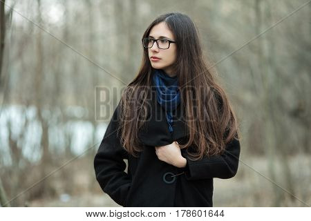 Young Beautiful Girl In A Black Coat Blue Scarf Glasses Exproring Autumn / Spring Forest Park. An El
