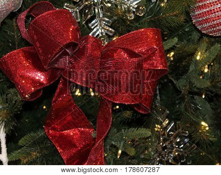 Glittery Red Bow Decorating a Christmas Tree