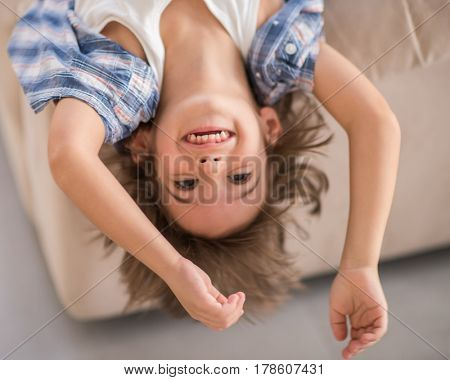 Upside down top view cute funny child closeup with long cute hair laughing on sofa at home
