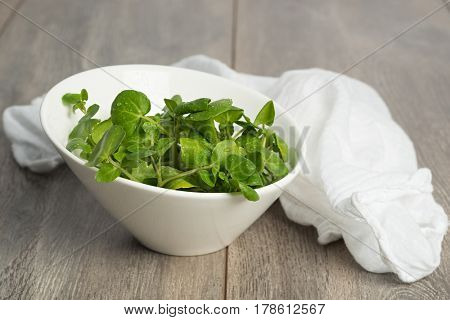 Fresh watercress in a bowl with white muslin cloth