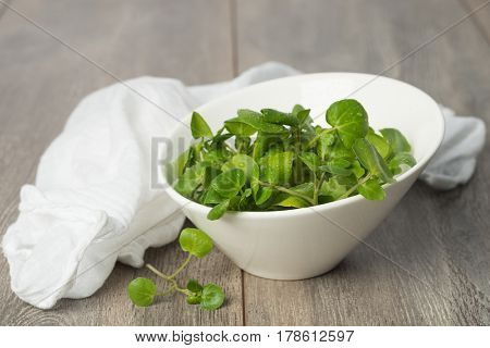 Fresh watercress in a bowl with white napkin