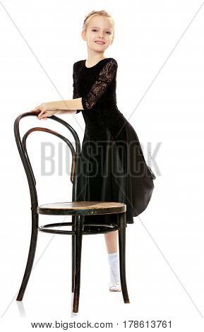 The slender little blonde girl dancer in the long dress of black color made specifically for performing .A girl stands in a half turn to the camera near the old Vienna chair.Isolated on white background.