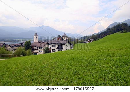 Travel To Sankt-wolfgang, Austria. The Green Meadow With The Houses In The Mountains.