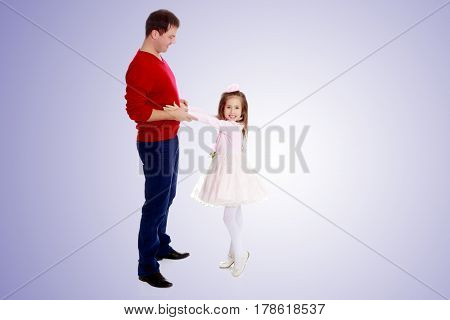 Cute little long-haired girl in a smart pink dress , reaches out to his dad.Purple gradient background.