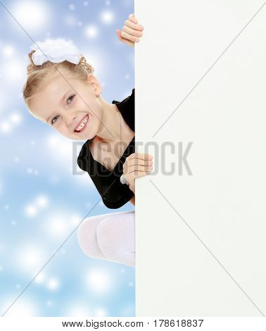Beautiful little blonde girl dressed in a white short dress with black sleeves and a black belt.The girl peeks out from behind white banner.Blue Christmas festive background with white snowflakes.