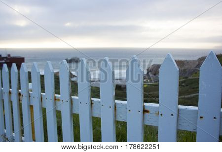 S white picket fence next to the Ocean.