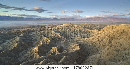Sunrise over jagged desert badlands with clouds