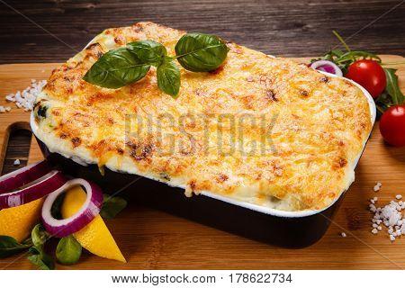 Lasagna served on cutting board