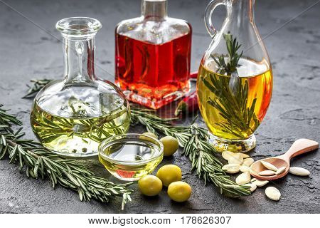 extra oil in carafe with spices, green olives and fresh chili on stone desk background