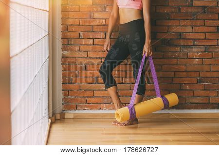 Unrecognizable woman in a yoga studio indoors, against a brick wall with a mat.