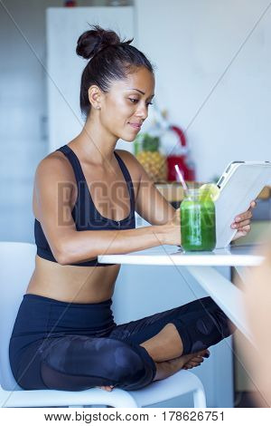 Woman drinking a homemade green detox juice, wearing sportive clothing.