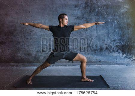 Man practicing advanced yoga against a dark wall