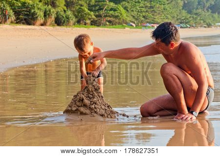 father and his little son building sand castle at beach