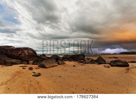 Sunset at tropical beach. Evening sea landscape under dramatic stormy sky. Thailand