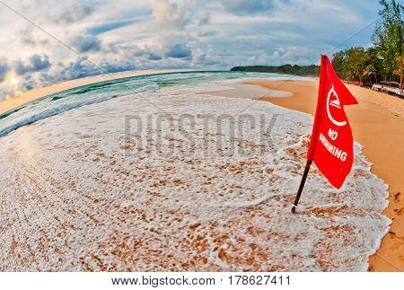 Red warning flag at beach in fish-eye. Phuket, Thailand.