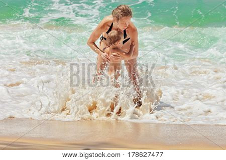 happy family of mother with kid playing in the sea waves