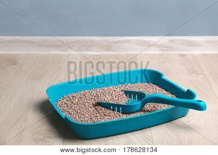 Plastic litter box with filler and scoop on floor
