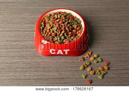 Cat food in bowl on wooden background