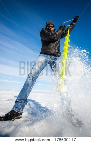 Person drilling ice in the winter for ice-fishing