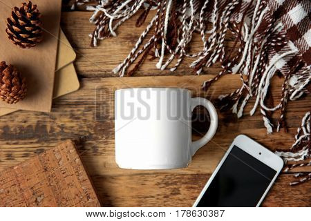 Composition with cup, phone,  cones and plaid on wooden background