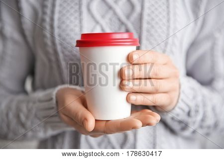Woman holding paper cup, closeup