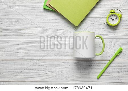Blank cup and office supplies on white wooden background