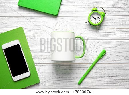 Blank cup, smartphone and office supplies on white wooden background