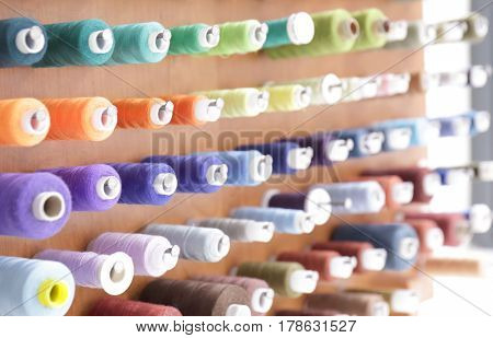 Spools with threads on rack, closeup