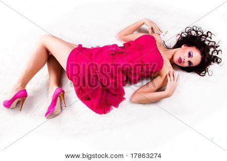 sexy girl wearing pink dress lies on white fur