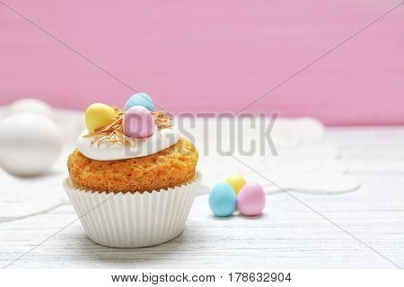 Delicious Easter cupcake on wooden table against blurred pink background