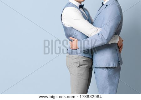Happy gay couple embracing on color background