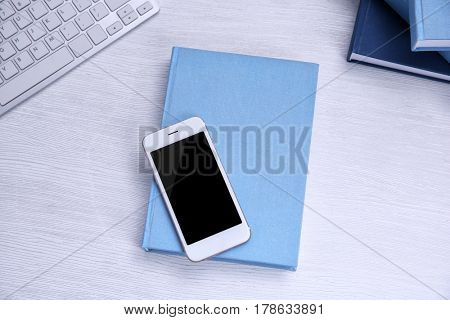 Book with smart phone on wooden background