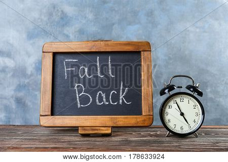 Chalkboard with text FALL BACK and retro alarm clock on wooden table