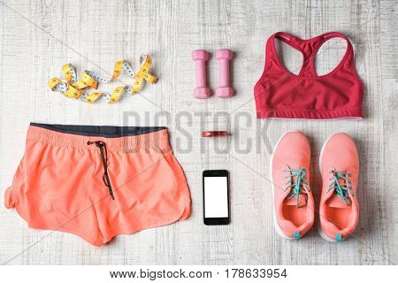 Clothes and fitness accessories on wooden background