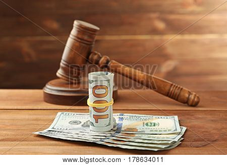 Money and judge's gavel on wooden background