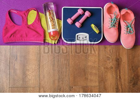 Fitness tracker and sports equipment on wooden floor, top view