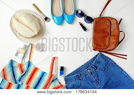 Set of stylish clothes and cosmetics for woman on white background
