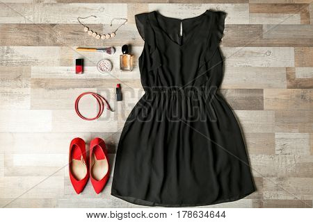 Stylish female clothes with accessories on wooden background