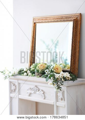 Beautiful composition with fresh flowers on mantelpiece