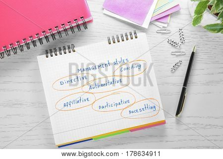 Notebook with MANAGEMENT STYLES diagram on wooden background