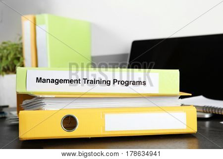 Folder with label MANAGEMENT TRAINING PROGRAMS on wooden table