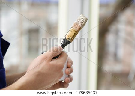 Hands of young worker going to paint window in office