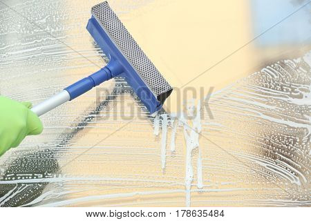 Hand of man with mop washing window outdoors
