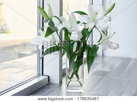 Vase with beautiful white lilies on windowsill