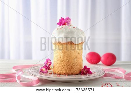 Plate with Easter cake and flowers on light background