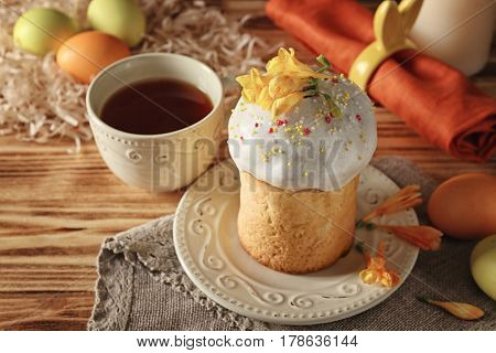 Plate with Easter cake and cup on wooden background