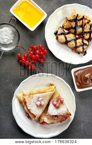 Delicious pancakes with chocolate and viburnum on plate